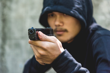 Robber with hood points the gun