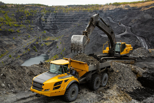 Excavator loads coal in a articulated dump truck. Heavy mining industry.