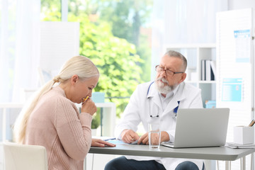 Coughing mature woman visiting doctor at clinic