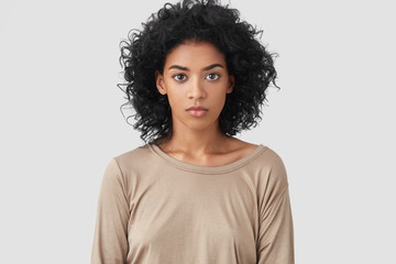 Indoor shot of serious dark skinned female freelancer has Afro hairstyle, pleasant appearance, dressed in beige casual sweater, works distantly at home, enjoys domestic atmosphere. Ethnicity concept Wall mural