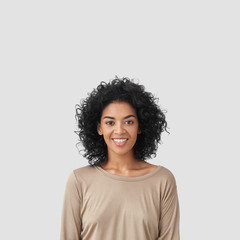 Smiling delighted young African American female has gentle smile, has white teeth, rejoices meeting with colleagues, dressed in casual clothes, isolated over white background with blank space