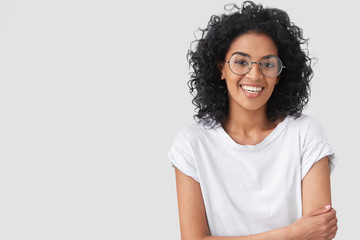 Waist up portrait of beautiful young dark skinned female with positive expression, has Afro hairdo, feels happy after successful bargain, wears big spectacles, isolated over white background