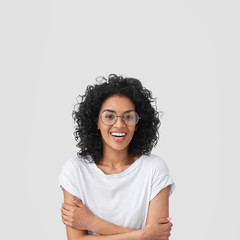 Glad female student has Afro hairstyle, broad smile, keeps hands crossed, wears glasses, happy to spend evening with family, wears t shirt in one tone with background. People and emotions concept