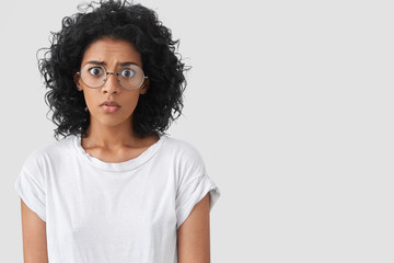 Frightened stupefied frustrated African American female looks in bewilderment with wide opened eyes, afraids of something, wears big spectacles, isolated over white background with copy space.