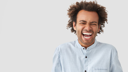 Comic mixed race young male has fun with friends, tell each other anecdotes, has toothy smile, frowns face from laughter, shows even teeth, being in high spirit. People and emotions concept.