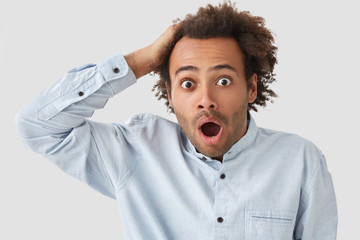 Emotive surprised African American male tourist scratches head, being shocked as doesn`t recieve visa for travelling abroad, feels stunned, dressed in white shirt. People and reaction concept