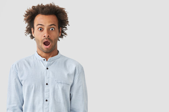 Studio shot of dark skinned mixed race young male being surprised to be accused of what he didn`t do, looks with popped eyes, isolated over white blank wall with free space for advertisement