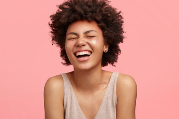 Beautiful African American woman laughs at something funny, has sparkles on cheeks, shows bare shoulders, closes eyes with pleasure, isolated over pink background. People and make up concept