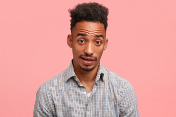 Confused attractive dark skinned male raises eyebrows in bewilderment, expresses surprisement, has beard and moustache, dressed in checkered shirt, isolated over pink background. Facial expressions