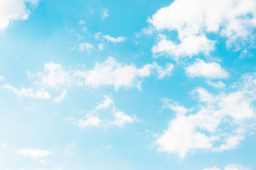 Blue sky with torn white formless clouds.