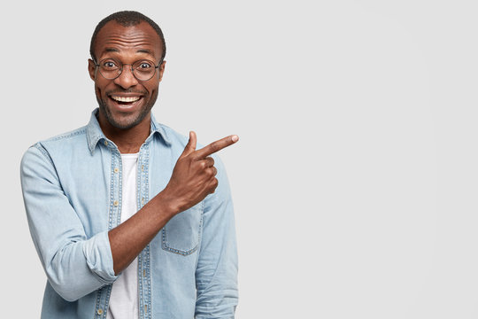 Positive dark skinned male has joyful expression and broad smile with white teeth, being in good mood, points at his new luxury car, rejoices purchase, isolated over studio wall with copy space