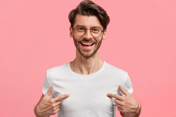 Horizontal shot of handsome cheerful hipster male indicates at white t shirt, shows blank space for your logo, being in high spirit, isolated over pink blank wall. Positive emotions and advertisement