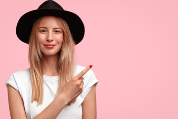 Portrait of pretty young female with pleased expression, wears black elegant hat, indicates with fore finger at upper right corner, shows blank space for your advertisement or promotional content