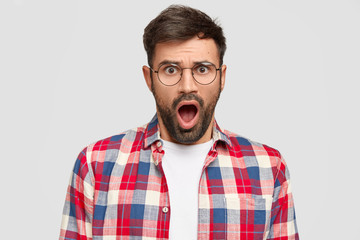 Portrait of stunned male manager has stupefied expression, opens mouth widely, stares at camera, feels astonishment, dressed in casual checkered shirt, isolated on white wall. Bearded man in glasses