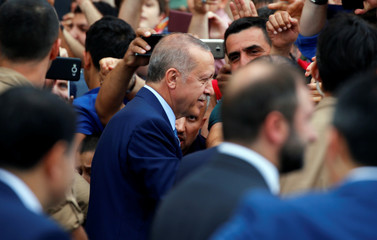 Turkish President Tayyip Erdogan talks to supporters as he leaves a polling station in Istanbul