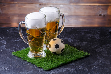 Picture of two glasses of beer, soccer ball on green grass