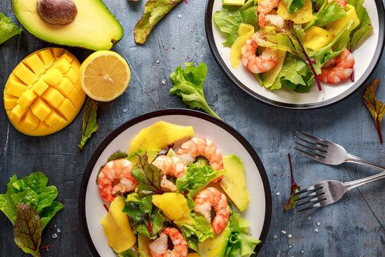 Fresh Shrimps, Avocado, Mango salad with lettuce green mix, herbs, lemon, healthy food.