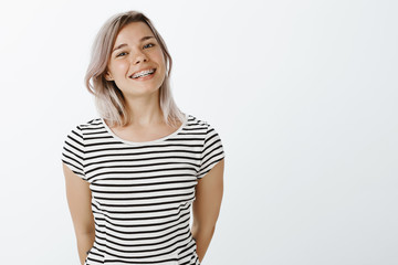 Studio shot of cute caucasian girlfriend with blond hair and braces on teeth standing in casual striped t-shirt and smiling broadly at camera, holding hands behind, enjoying great sunny day