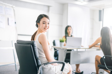 Smiling young asian business woman working in office.