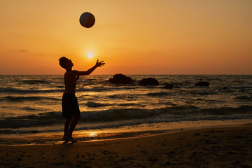 Silhouette of man playing football on the beach