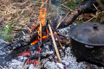 Сauldron on a bonfire. Outdoor touristic cooking concept on open fire. Old fashioned way to make food.