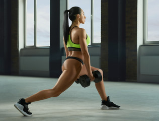 Sideview of athletic girl performing fallouts keeping dumbbells in spacy gym with panoramic windows. Having strong, fit body with heatlthy tanned skin, muscles. Doing fitness exercises.