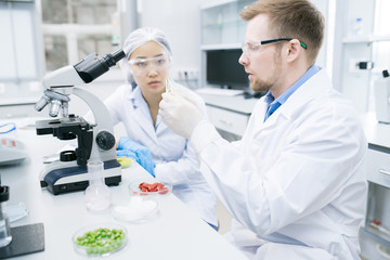 Crop view of microbiologists in laboratory coats and glasses sitting at white table with microscope and looking excitedly at sample of meat in pincers held by man.