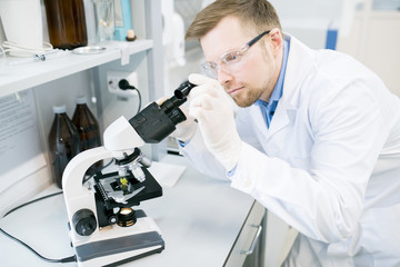 Crop view of man in glasses and laboratory coat standing at desk and looking at eyepiece of microscope with green vegetable sample lying on it