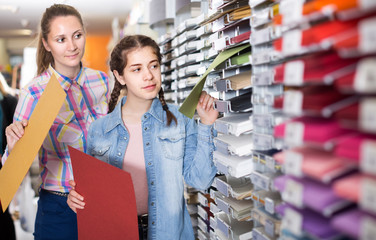 woman and girl shopping multicolored paper in art store