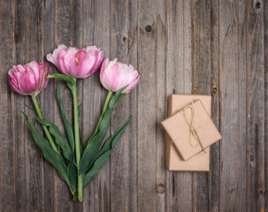 Pink terry tulips and craft gift box on rustic wooden background, Valentines Day or Mothers day background, top view.