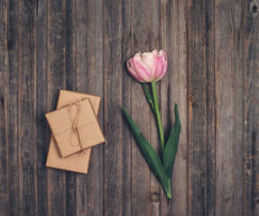 Pink terry tulip and craft gift box on rustic wooden background, Valentines Day or Mothers day background, top view.