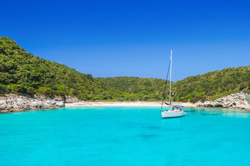 Beautiful beach with sailing boat, Antipaxos island, Greece