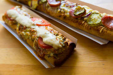Polish zapiekanka toasted baguette with cheese and vegetables
