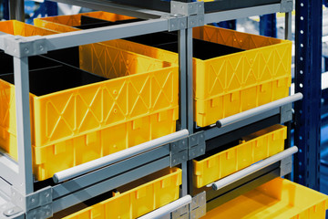 Yellow plastic boxes in the cells of the automated warehouse.