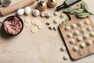 Raw homemade dumplings at cutting board