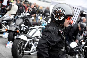 """A man wearing a helmet stands in front of Harley-Davidson bikes at the """"Hamburg Harley Days"""" in Hamburg"""