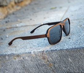 Sunglasses in a wooden frame on gray stone steps.