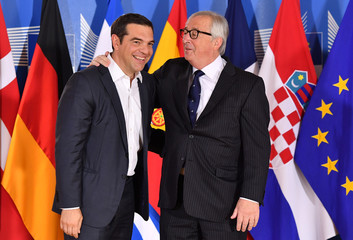 European Commission President Jean-Claude Juncker speaks with Greek Prime Minister Alexis Tsipras during an informal EU summit on migration at EU headquarters in Brussels