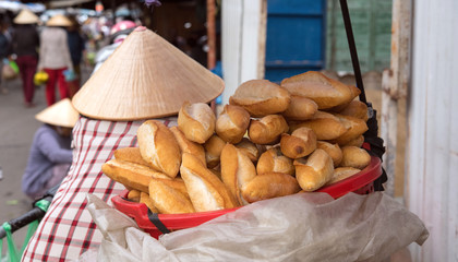 French baguette seller at outdoor market in Hoi An, Vietnam