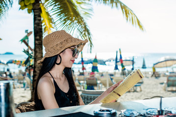 Beautiful Asia woman wearing black dress and a brown hat Holding a menu at the Beach Club near Beach. Portrait sexy asian woman relax on holiday.