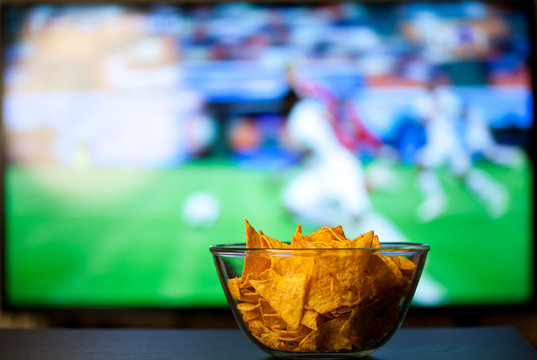 beer glasses and chips in front of tv - watching world cup football at home - soccer supporters