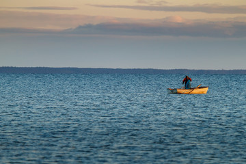 Fisherman in his small boat on the ocean