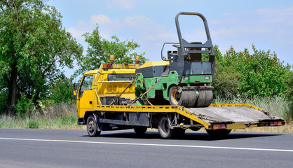 Ukraine, Odessa. June 15, 2018. The route Odessa - Nikolaev. Tow truck and asphalt roller on the city road.