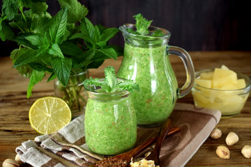 Green smoothie in a glass jar and jug topped with mint
