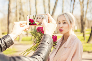 Photographer making photo with smartphone. Phone display with fashion photo young woman
