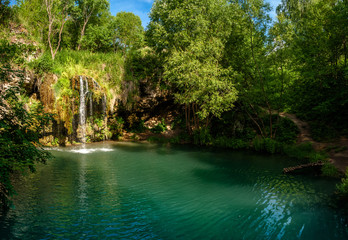 Waterfall and a beautiful lagoon lake for relaxing in the summer forest.