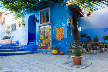 Blue walls of Chefchaouen city medina in Morocco with bright doors and colorful flower pots on the walls with sun light