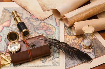 Planning a trip: quill pen, old rolled papers and maps with vintage items