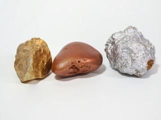 gold, bronze and silver nugget precious stone on white background