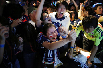 Japanese fans react as they watch a broadcast of the World Cup Group H soccer match Japan vs Senegal, at a sports bar in Tokyo